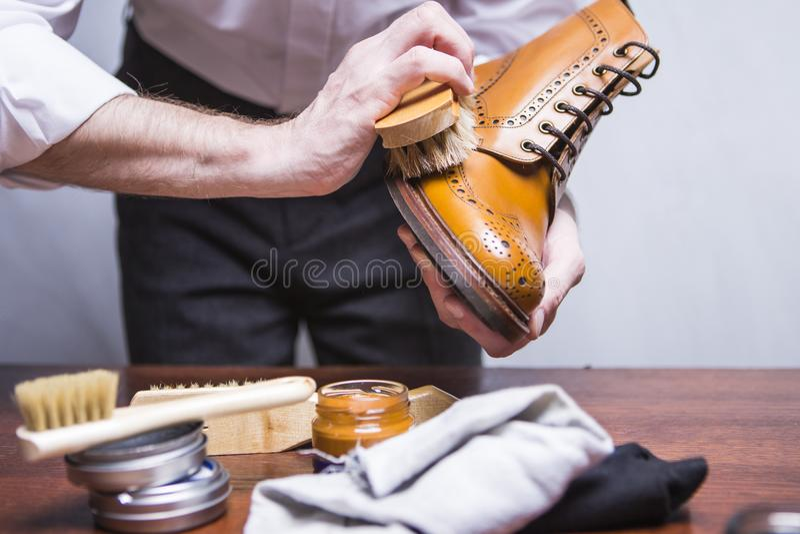 Manos del limpiador masculino profesional del calzado que usa el cepillo para polaco imagen de archivo libre de regalías