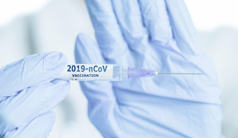 Manos del médico en guantes que muestran la jeringa con la vacunación 2019-nCoV foto de archivo