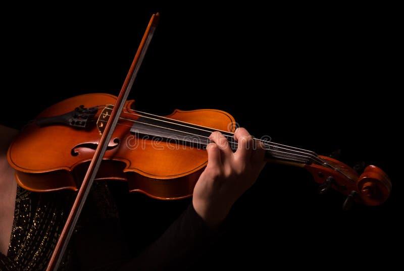 Manos del músico que tocan el violín aislado en negro imagenes de archivo