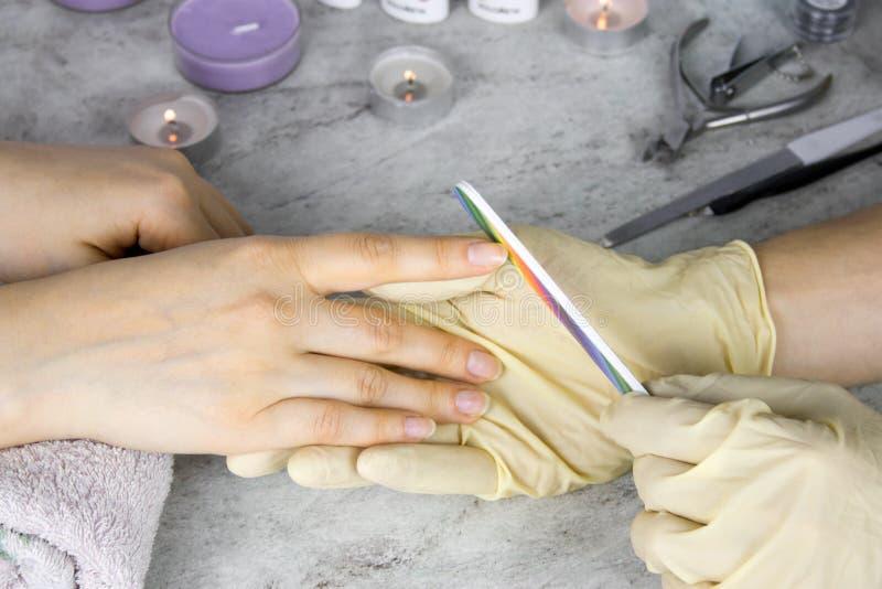 manos del manicuro en guantes con el fichero de clavo que lleva a cabo las manos del cliente, del proceso de la manicura y del cu foto de archivo