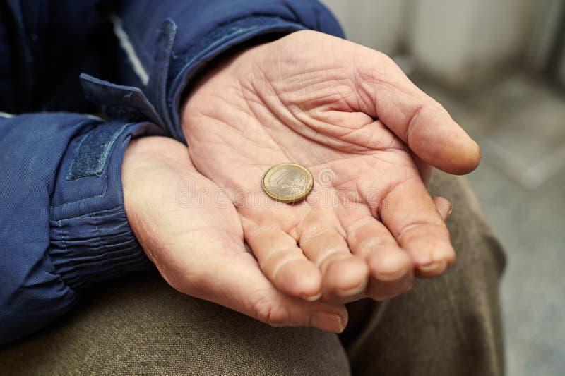 Manos del mendigo con una moneda euro que pide dinero foto de archivo