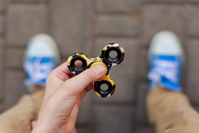 Manos del muchacho desconocido que juegan con el hilandero de la persona agitada, cierre para arriba Tren imagen de archivo