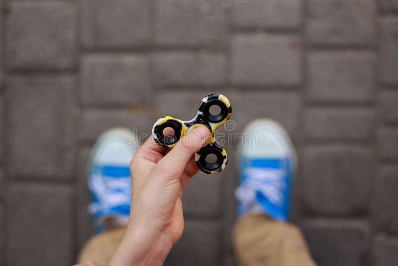 Manos del muchacho desconocido que juegan con el hilandero de la persona agitada, cierre para arriba Tren imagen de archivo libre de regalías