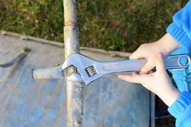 Manos del muchacho que atornillan el tornillo con la llave fotos de archivo