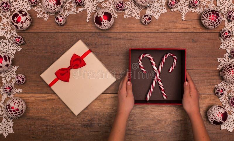 Manos del niño con la caja de regalo de la Navidad que contiene los bastones de caramelo imagen de archivo