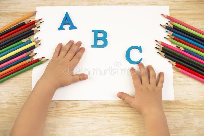 Manos del niño en la tabla Concepto de la educación y del alfabeto Lápices en un fondo de madera fotos de archivo