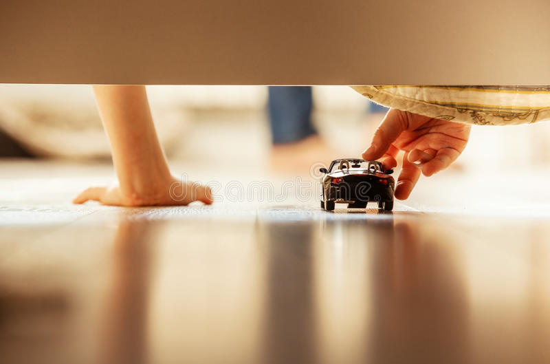 Manos del niño pequeño de la imagen del primer con el coche del juguete imagen de archivo