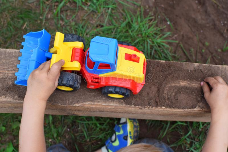 Manos del niño pequeño que juegan con el coche del juguete imagen de archivo libre de regalías