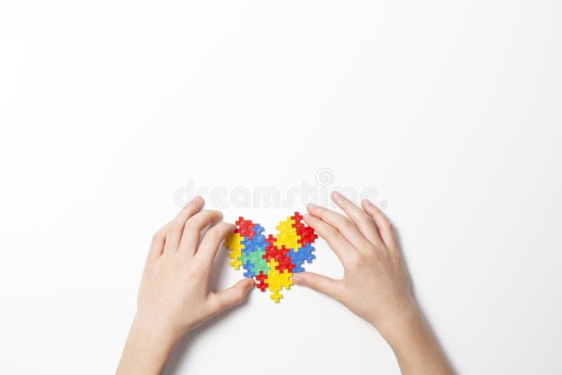 Manos del niño que llevan a cabo el corazón colorido en el fondo blanco Concepto del día de la conciencia del autismo del mundo fotos de archivo