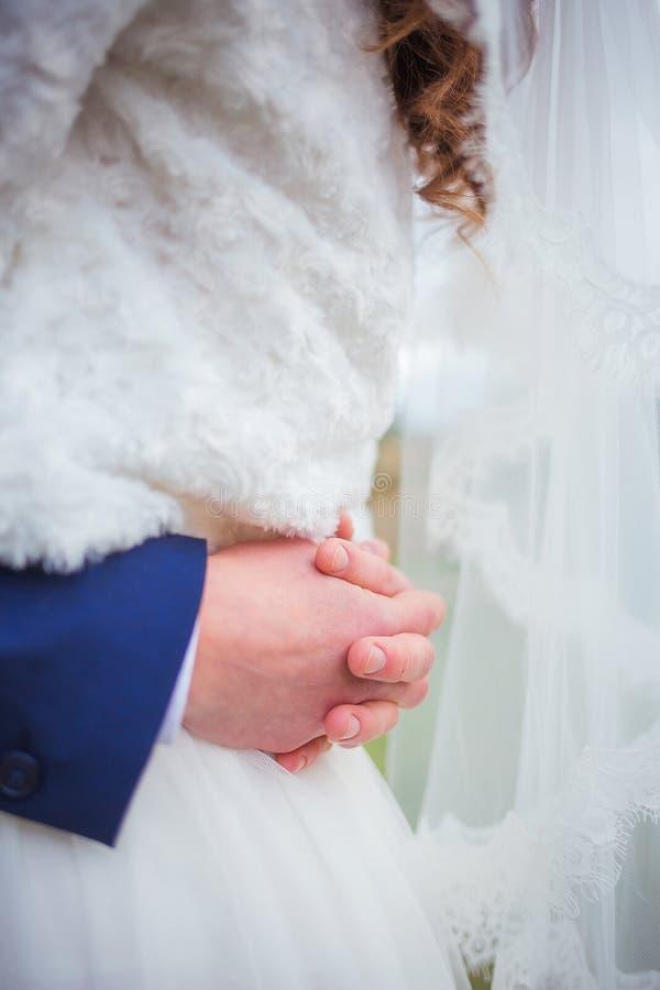 Manos del novio que abrazan a la novia fotos de archivo