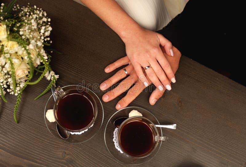Manos del novio y de la novia con los anillos en la tabla con dos tazas de café, opinión superior del primer foto de archivo libre de regalías