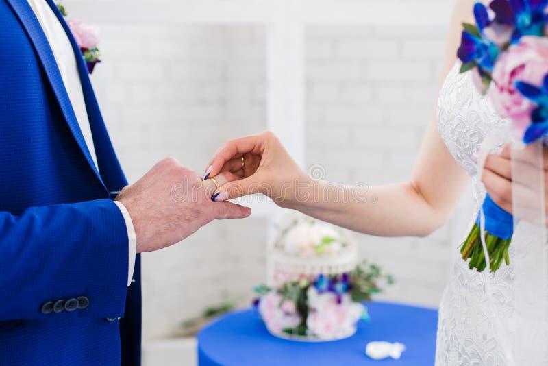 Manos del novio y de las novias que llevan los anillos de bodas, opinión del primer imagenes de archivo