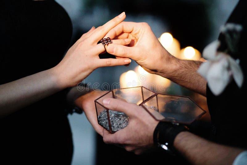 Manos del novio y de las novias que llevan los anillos de bodas, opinión del primer fotos de archivo