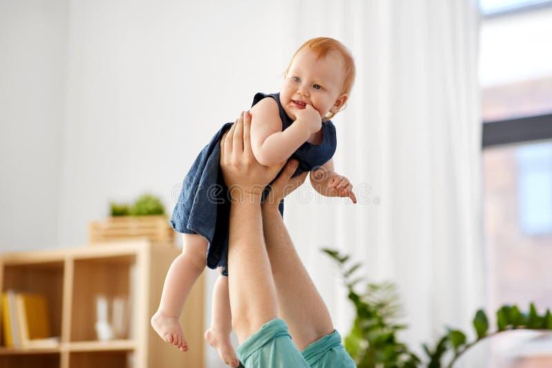 Manos del padre que detienen al bebé pelirrojo en casa imagenes de archivo