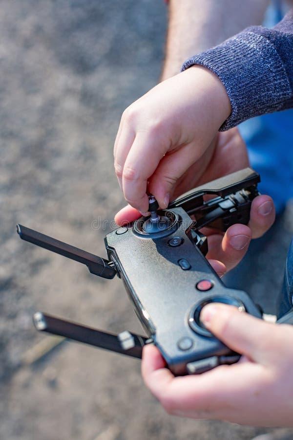 Manos del padre y del hijo que sostienen la palanca de mando teledirigida y que pilotan el quadrocopter fotografía de archivo