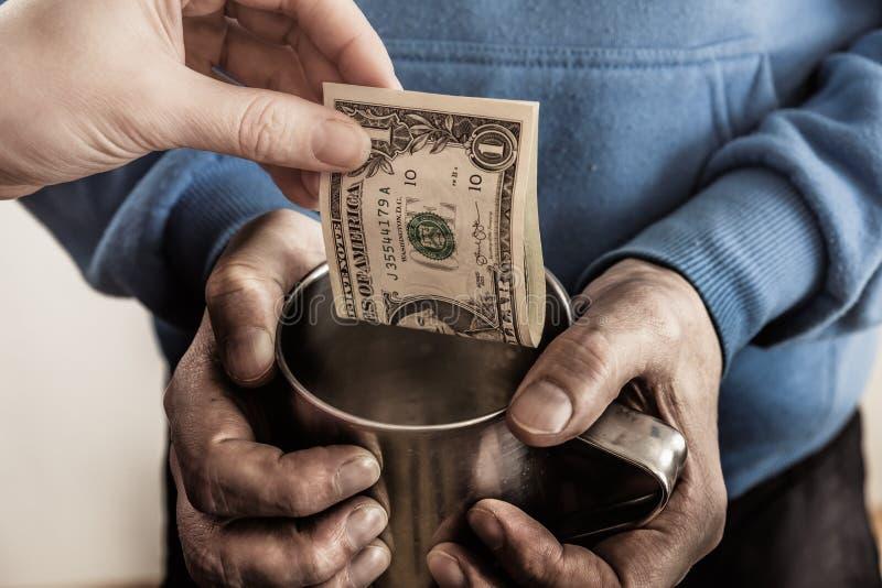 Manos del primer con las manos sucias de la taza de un hombre sin hogar del mendigo y de un billete de dólar de limosnas fotos de archivo