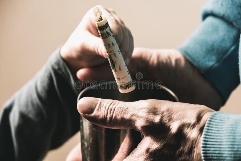 Manos del primer con las manos sucias de la taza de un hombre sin hogar del mendigo y de un billete de dólar de limosnas fotografía de archivo libre de regalías