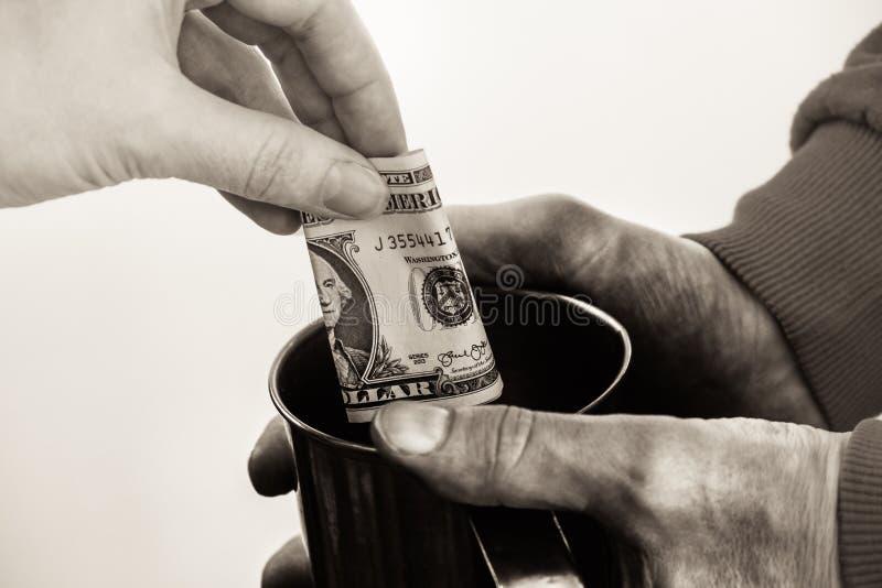 Manos del primer con las manos sucias de la taza de un hombre sin hogar del mendigo y de un billete de dólar de limosnas imagen de archivo libre de regalías
