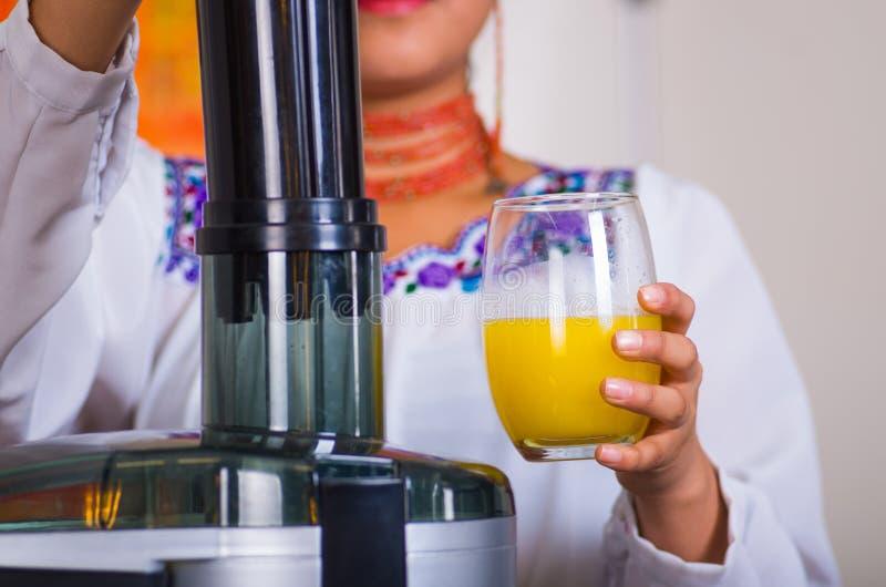 Manos del primer de la mujer que se sostienen de cristal con el zumo de naranja, la otra mano que descansa sobre la máquina, conc foto de archivo libre de regalías