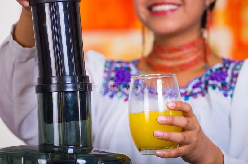 Manos del primer de la mujer que se sostienen de cristal con el zumo de naranja, la otra mano que descansa sobre la máquina, conc fotos de archivo libres de regalías