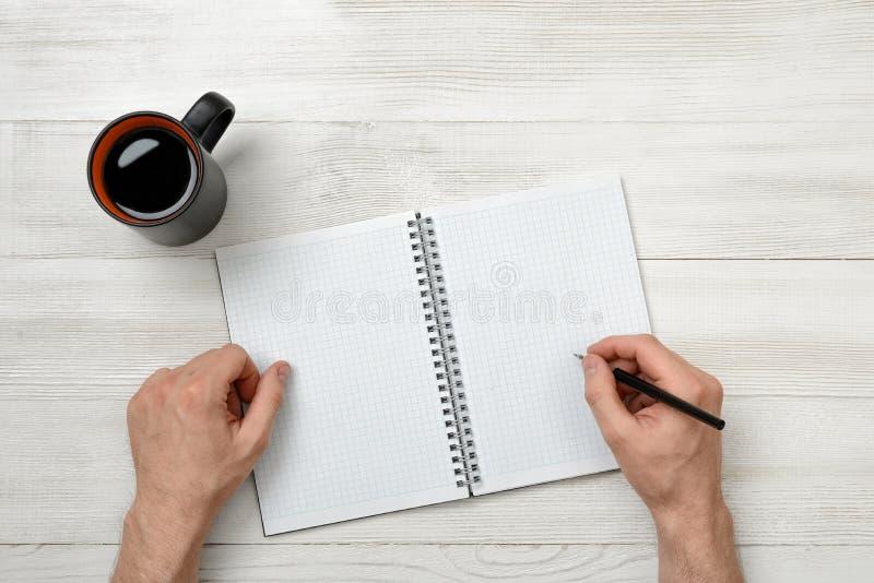 Manos del primer de la pluma de tenencia del hombre sobre el cuaderno vacío con café de la taza al lado de él imagen de archivo libre de regalías