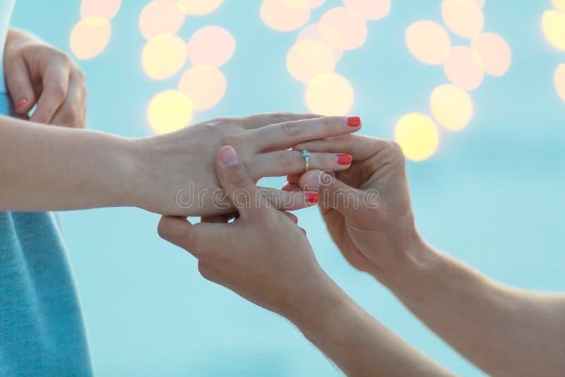 manos del primer El individuo hace la muchacha una propuesta de matrimonio en la tarde en desierto de la arena foto de archivo