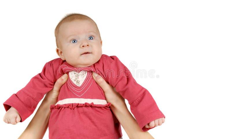 Manos del ` s de la madre que detienen al bebé lindo imagen de archivo