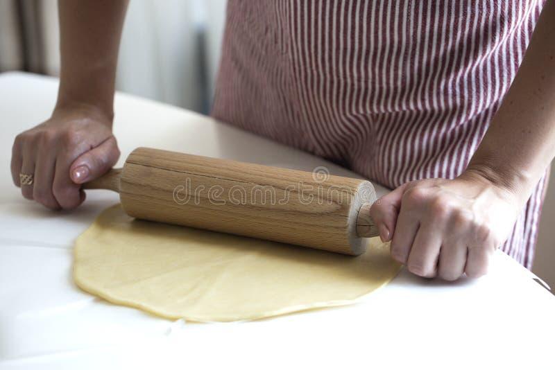 Manos del ` s de las mujeres con el rodillo Las manos del ` s de las mujeres ruedan la pasta encendido fotos de archivo