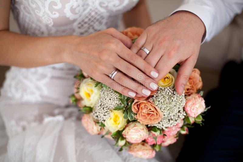 Manos del ` s de novia y del novio con los anillos de bodas Primer fotos de archivo libres de regalías