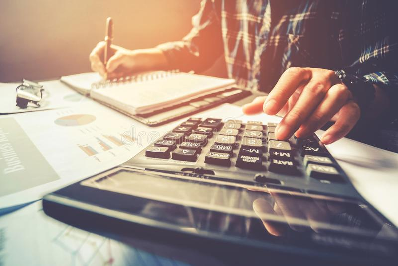 Manos del ` s del hombre de negocios con la calculadora en la oficina y financiero foto de archivo