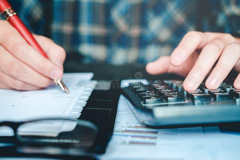 Manos del ` s del hombre de negocios con la calculadora en la oficina y financiero fotografía de archivo