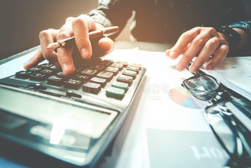 Manos del ` s del hombre de negocios con la calculadora en la oficina y financiero imagenes de archivo