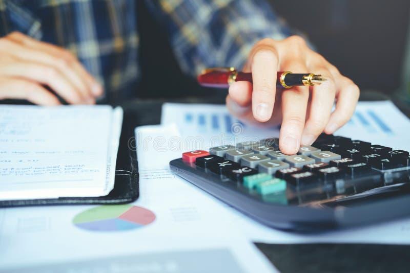 Manos del ` s del hombre de negocios con la calculadora en la oficina y financiero fotos de archivo libres de regalías