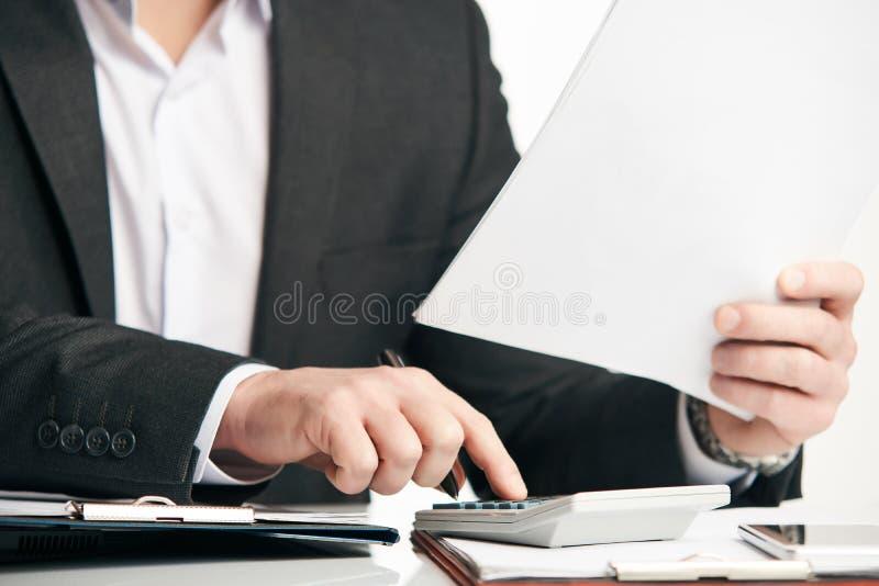 Manos del ` s del hombre de negocios usando la calculadora foto de archivo