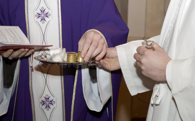 Manos del sacerdote en la bendición del petróleo fotos de archivo libres de regalías