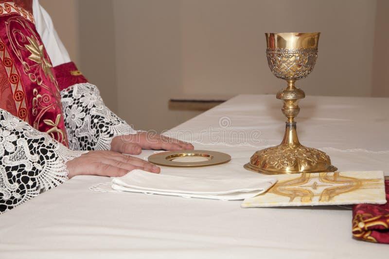 Manos del sacerdote por la masa imagenes de archivo