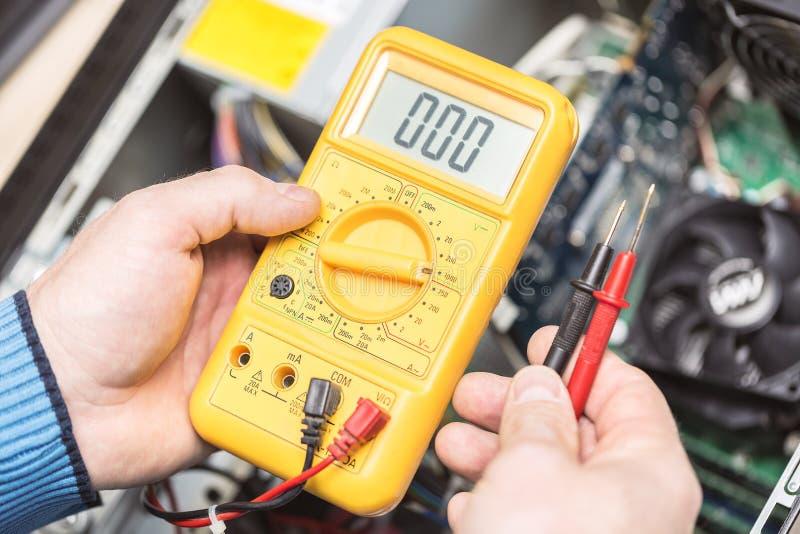 Manos del técnico que sostienen el voltímetro sobre la placa madre del ordenador Reparación del concepto de los ordenadores Enton fotografía de archivo libre de regalías