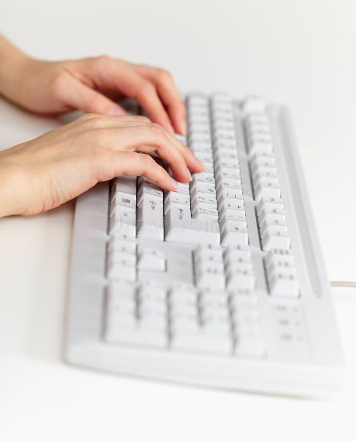 Manos del teclado y de la hembra de ordenador que trabajan en ella foto de archivo