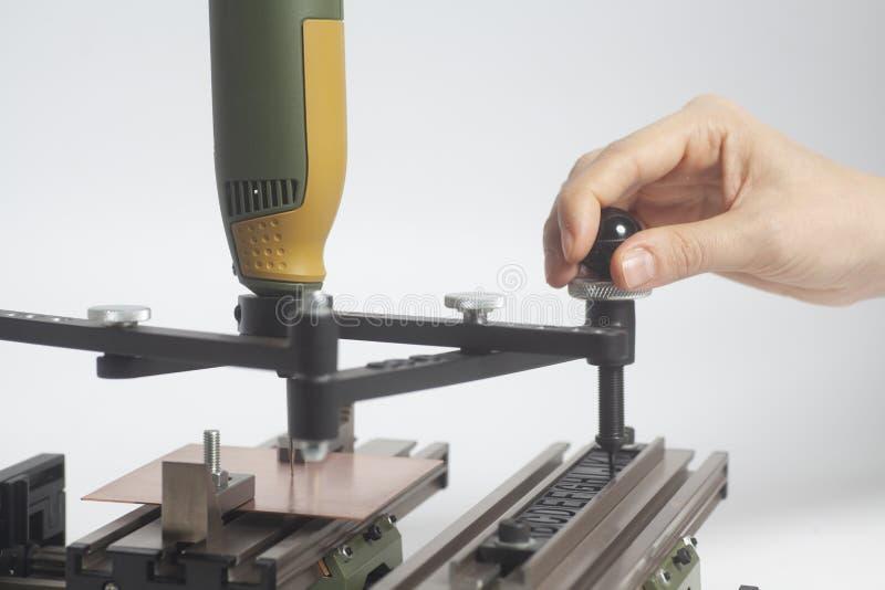 Manos del trabajador en el grabado del pantógrafo del dispositivo con el grabador del CNC con alfabeto de la prensa de copiar imagenes de archivo