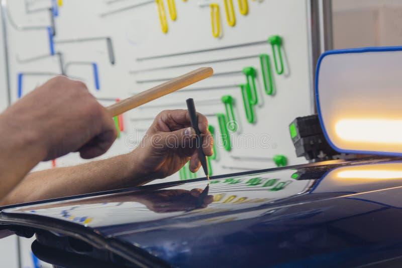 Manos del trabajador que trabaja en enderezar el coche fotografía de archivo libre de regalías