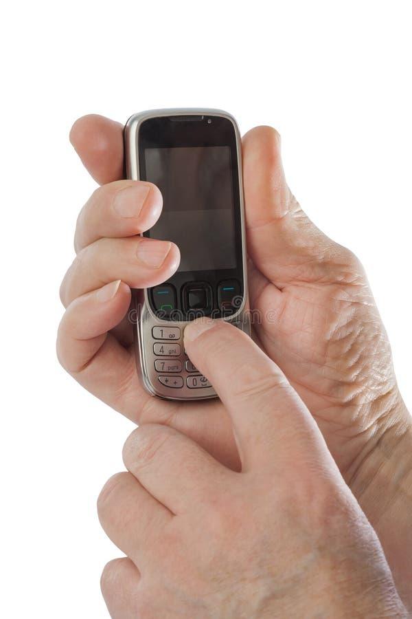 Manos del viejo hombre con el teléfono móvil viejo foto de archivo