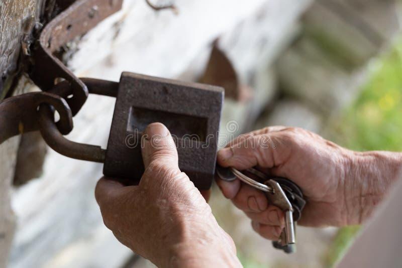 Manos del viejo hombre que llevan a cabo la cerradura y la llave del vintage del metal para abrir la puerta de madera vieja cerca foto de archivo libre de regalías