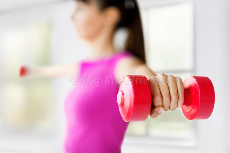 Manos deportivas de la mujer con pesas de gimnasia rojas claras fotos de archivo libres de regalías