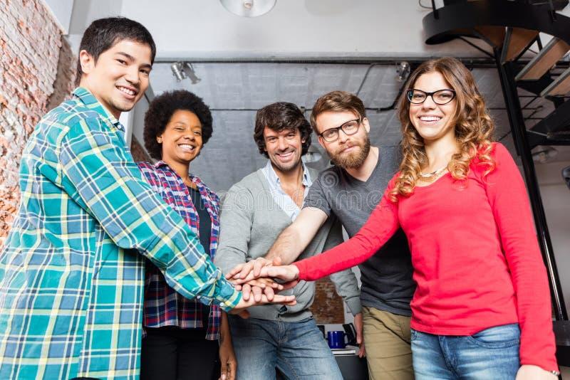 Manos diversas del equipo de la gente encima de uno a ayuda foto de archivo libre de regalías