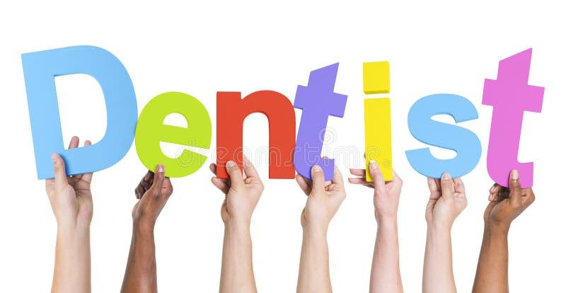 Manos diversas que detienen al dentista de la palabra imágenes de archivo libres de regalías