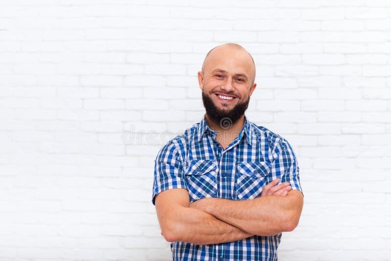 Manos dobladas sonrientes del hombre barbudo casual foto de archivo