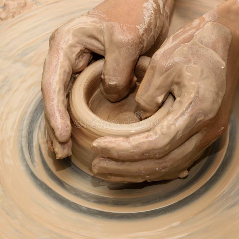Manos en arcilla en el proceso de la fabricación de cerámica en la rueda de la cerámica imágenes de archivo libres de regalías