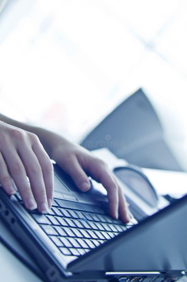 Manos en el ordenador portátil fotografía de archivo libre de regalías