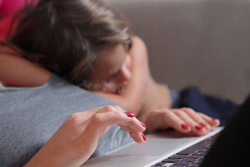 manos en el ordenador y en el fondo un bebé durmiente fotos de archivo