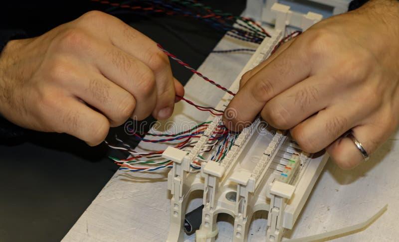 Manos en el trabajo en práctica de cableado de la red en una sala de clase de la tecnología de la información fotos de archivo libres de regalías